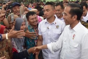 Presiden Jokowi menyambut uluran tangan warga saat menghadiri acara penyerahan 3.000 sertifikat hak tanah, di di GOR Tri Sanja, Tegal, Jawa Tengah, Jumat (9/11) pagi. (Foto: OJI/Humas)
